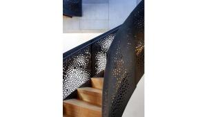 Escalera con barandas metalicas con pequeñas formas en corte laser.
